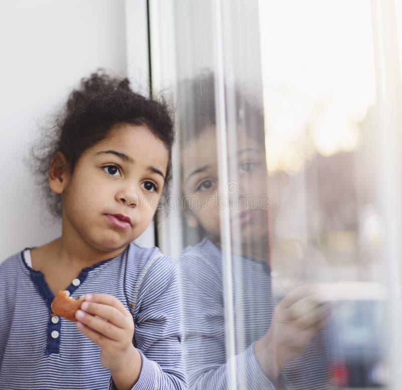 Menina triste que olha para fora a janela imagem de stock