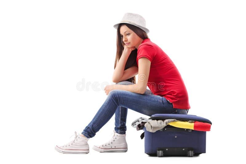 Menina triste que senta-se em uma pasta completamente da roupa imagem de stock