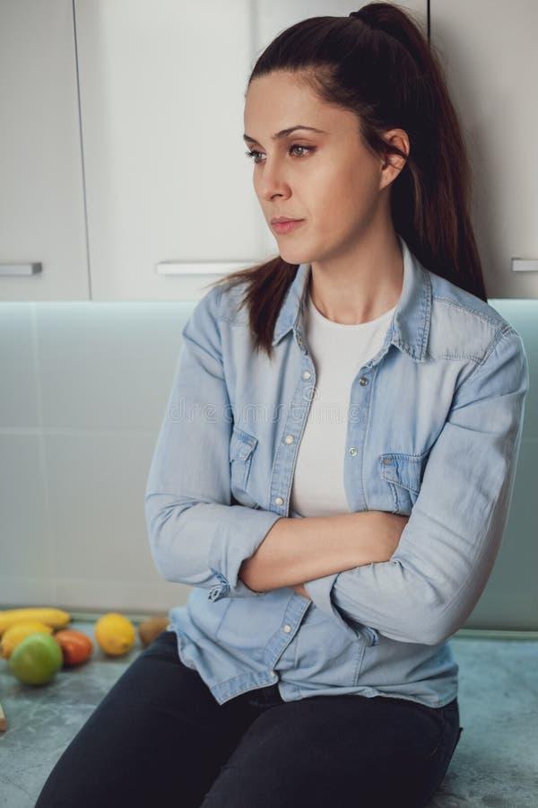 Menina triste que senta-se na bancada da cozinha imagens de stock royalty free