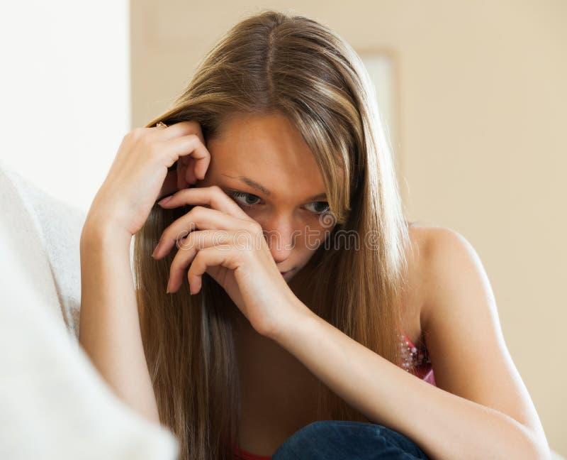 Menina triste que senta-se no sofá imagem de stock royalty free