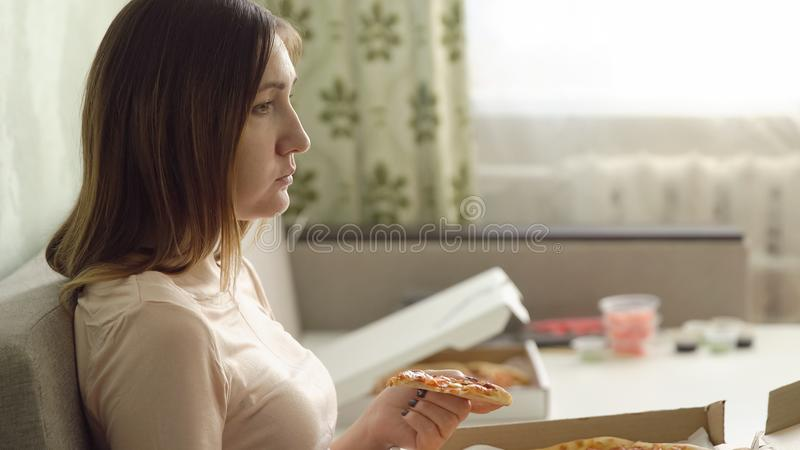 Menina triste só com a pizza que senta-se no sofá em casa e nos relógios um filme fotografia de stock royalty free