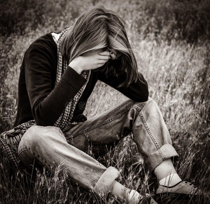 Menina triste só que senta-se na terra fotografia de stock royalty free
