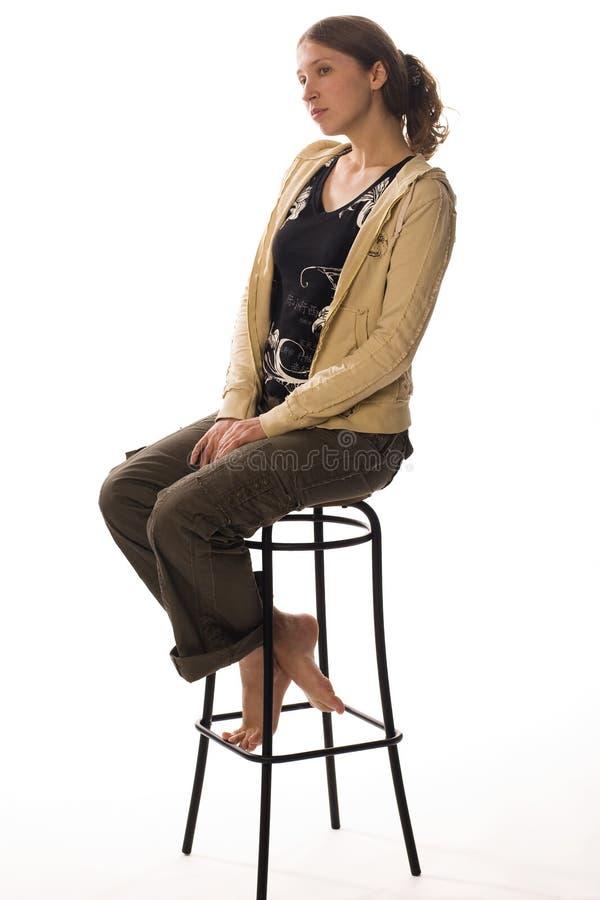 A menina triste senta-se no tamborete imagem de stock royalty free