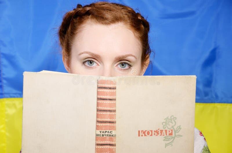 Menina ucraniana com um livro famoso imagem de stock royalty free