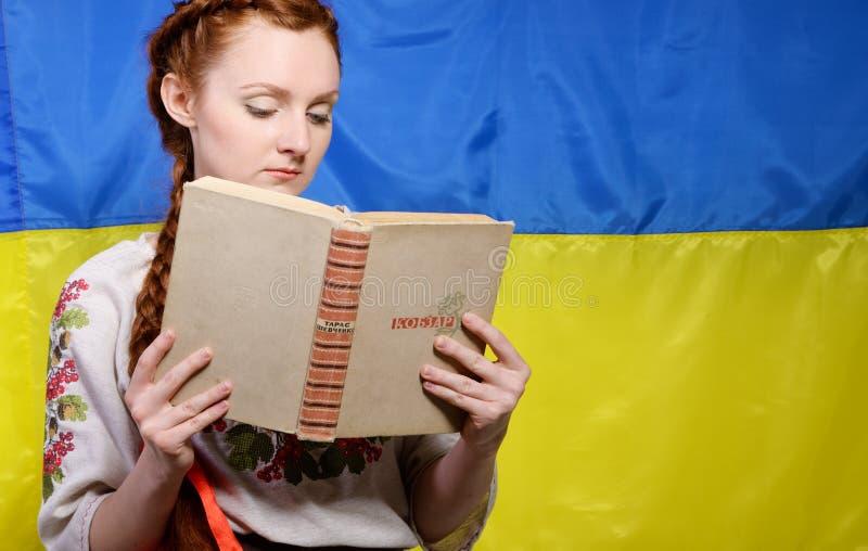Menina ucraniana com um livro famoso imagem de stock