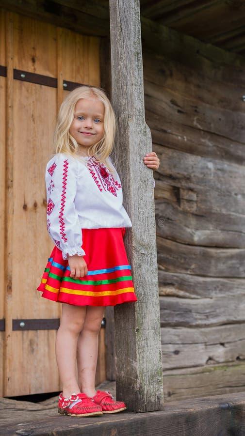 Menina ucraniana pequena que está perto da casa de madeira nacional velha imagem de stock royalty free