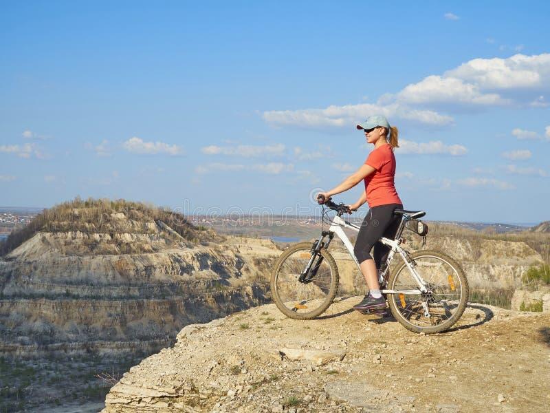 Menina uma bicicleta nas montanhas fotos de stock royalty free
