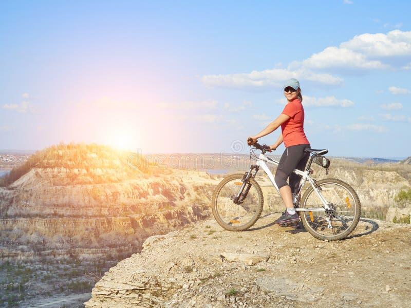 Menina uma bicicleta nas montanhas imagens de stock
