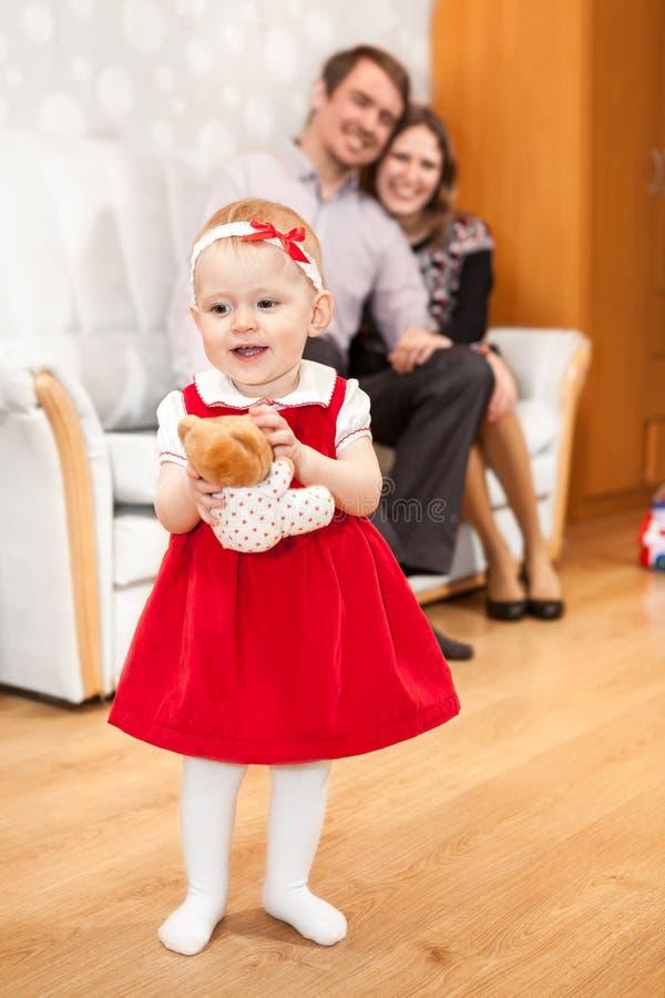 Menina uma criança que está no assoalho da sala de visitas, da mãe e do pai no sofá fotos de stock royalty free