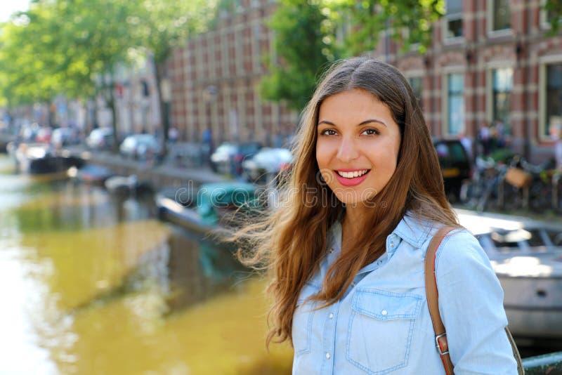 Menina urbana de sorriso na ponte que olha a câmera Mulher bonita nova que veste a camisa ocasional das calças de brim em Amsterd imagens de stock