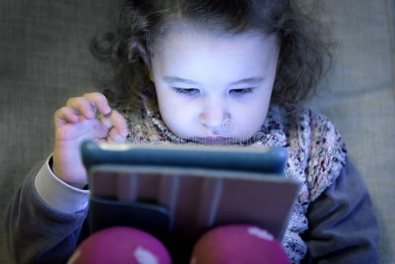 A menina usa uma tabuleta digital fotografia de stock