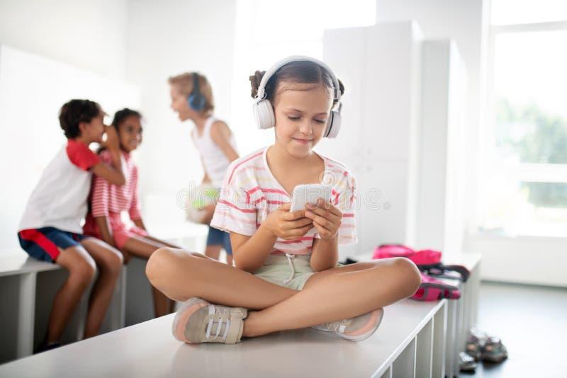 Menina usando fones de ouvido ouvindo música e usando smartphone imagens de stock royalty free