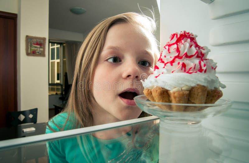 A menina vê o bolo doce no refrigerador fotos de stock royalty free