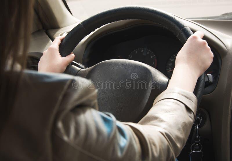 A menina vai atr?s da roda de um carro, m?os no volante Conduzindo um grande carro imagens de stock