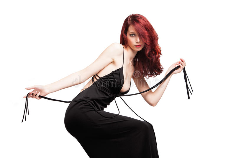 Menina vermelha atrativa elegante do cabelo no estúdio preto do vestido fotografia de stock
