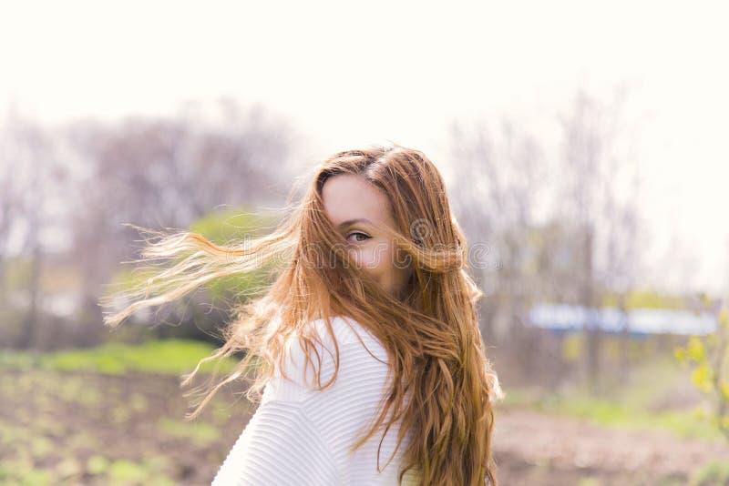 Menina vermelha bonita com cabelo no movimento exterior no dia ensolarado imagens de stock