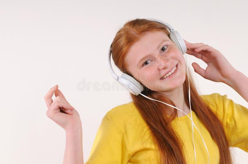 Menina vermelha nova bonita do cabelo com os fones de ouvido que relaxam pela música de escuta fotografia de stock royalty free