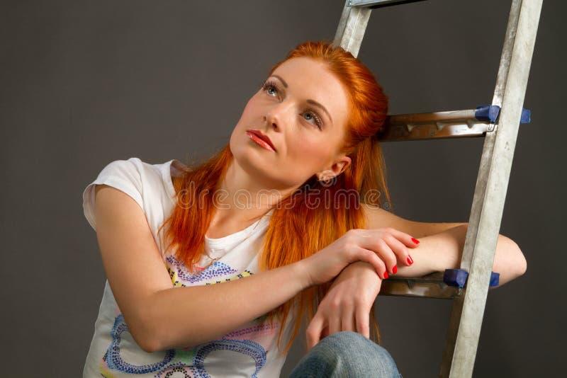 Menina vermelho-de cabelo nova bonita que inclina-se em uma escada fotografia de stock royalty free