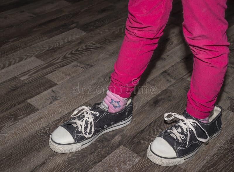 A menina veste um par de sapatas maiores imagens de stock royalty free