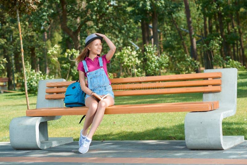 Menina vestida à moda nova que senta-se no banco que mantém um livro fotos de stock