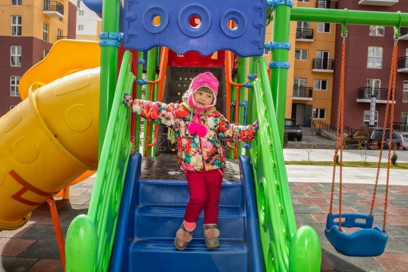 A menina, vestida calorosamente, em jogos de um chapéu e do revestimento no campo de jogos com corrediças e balanços no pátio do  fotografia de stock