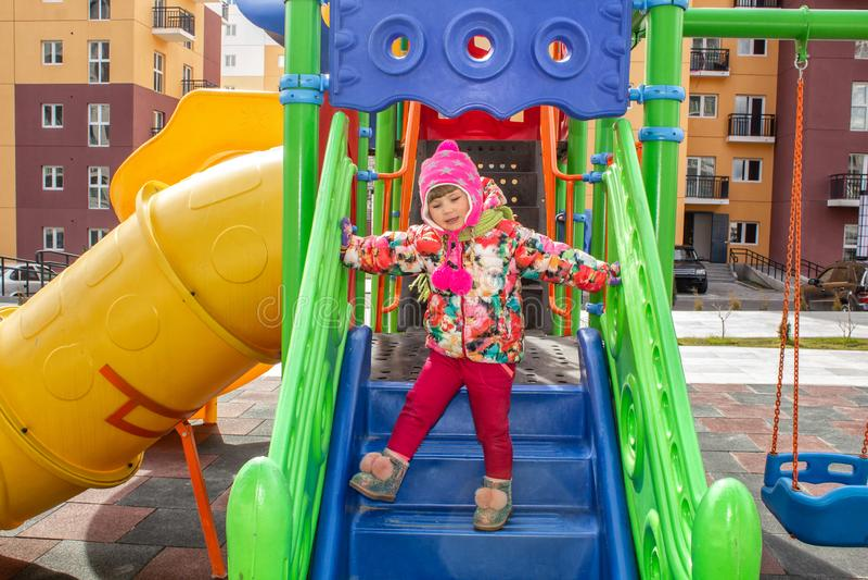 A menina, vestida calorosamente, em jogos de um chapéu e do revestimento no campo de jogos com corrediças e balanços no pátio do  fotos de stock
