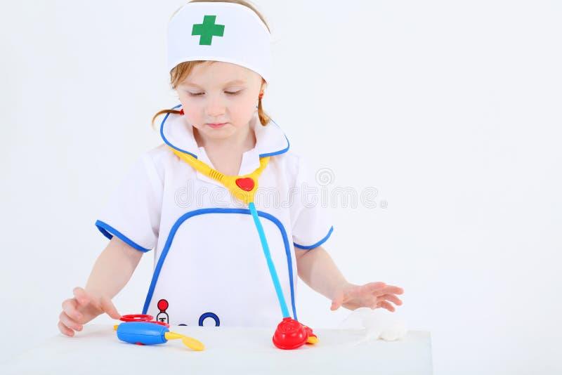 A menina vestida como a enfermeira joga com os instrumentos médicos do brinquedo foto de stock