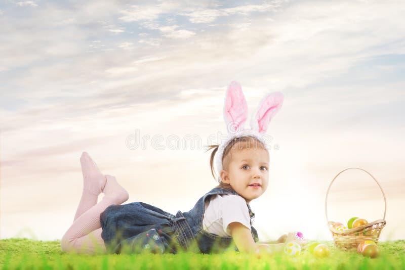 Menina vestida como o coelhinho da Páscoa que encontra-se na grama com fotografia de stock