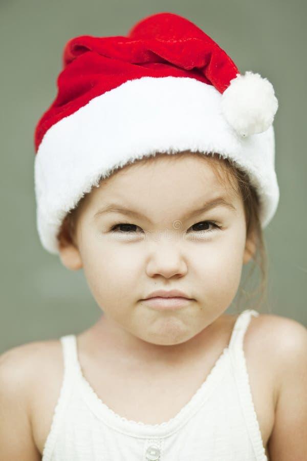 A menina vestida como um Papai Noel foto de stock