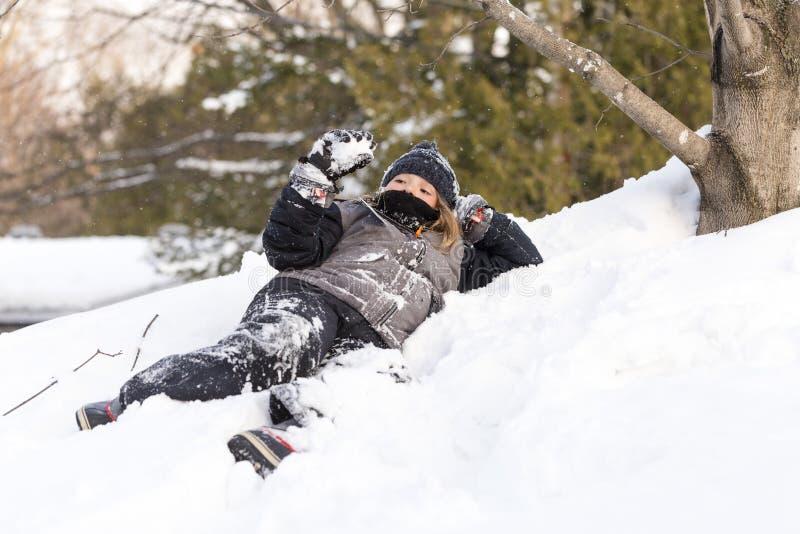 Menina vestida na roupa do inverno que encontra-se para baixo na bola de neve da terra arrendada do banco da neve fotos de stock royalty free