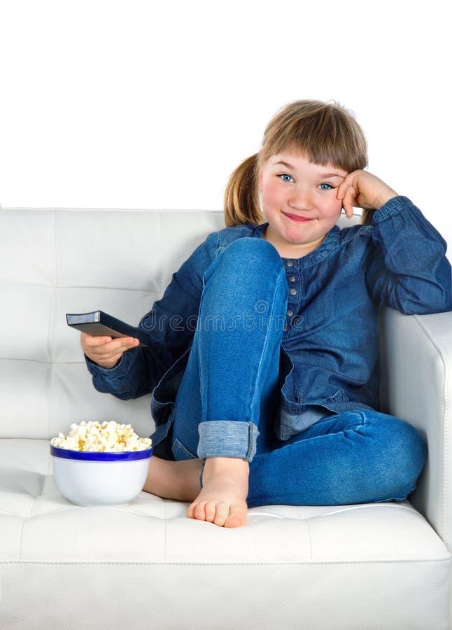 Menina vestida na sarja de Nimes azul que presta atenção à tevê fotos de stock