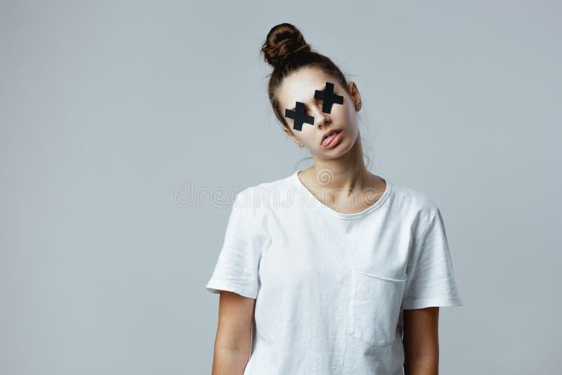 A menina vestida no t-shirt branco com cruzes pretas da fita adesiva nos olhos está levantando como um zombi no branco fotos de stock royalty free