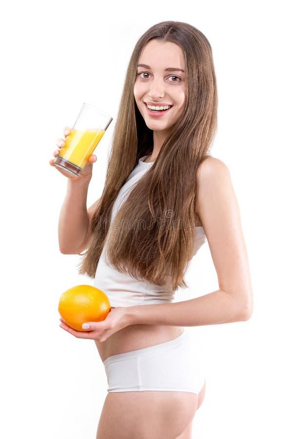 A menina vestiu-se em um suco de laranja bebendo da camisa branca contra um wh foto de stock royalty free