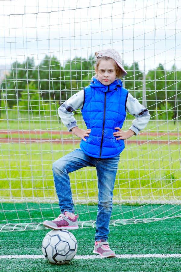 A menina vestiu-se na calças de ganga e no revestimento sem mangas que estão na porta do futebol e pôs-se seu pé sobre a bola imagens de stock