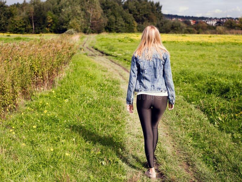 A menina vestiu-se nas caneleiras e no revestimento da sarja de Nimes que anda na estrada secundária imagem de stock royalty free