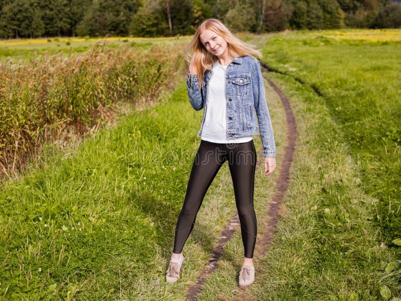 A menina vestiu-se nas caneleiras e no revestimento da sarja de Nimes que anda na estrada secundária fotos de stock royalty free