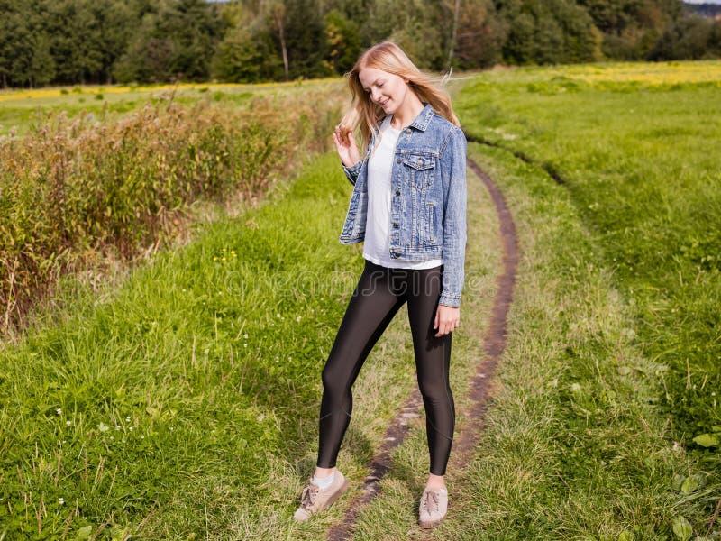 A menina vestiu-se nas caneleiras e no revestimento da sarja de Nimes que anda na estrada secundária imagens de stock