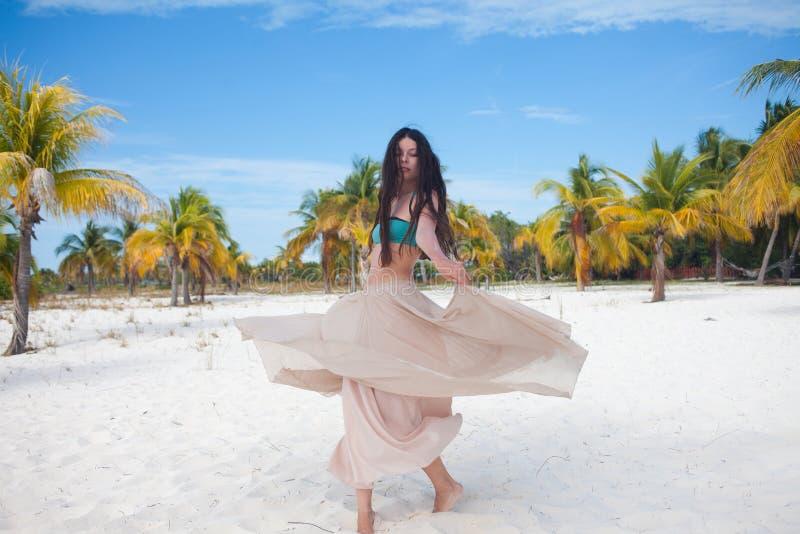 A menina viaja ao mar e está feliz Dança moreno atrativa nova da mulher que acena sua saia contra a paisagem tropical imagens de stock