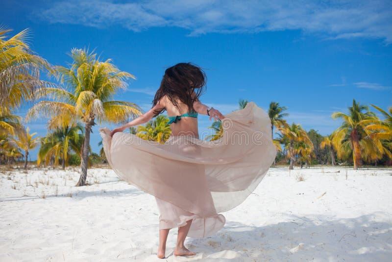 A menina viaja ao mar e está feliz Dança moreno atrativa nova da mulher que acena sua saia contra a paisagem tropical fotos de stock royalty free