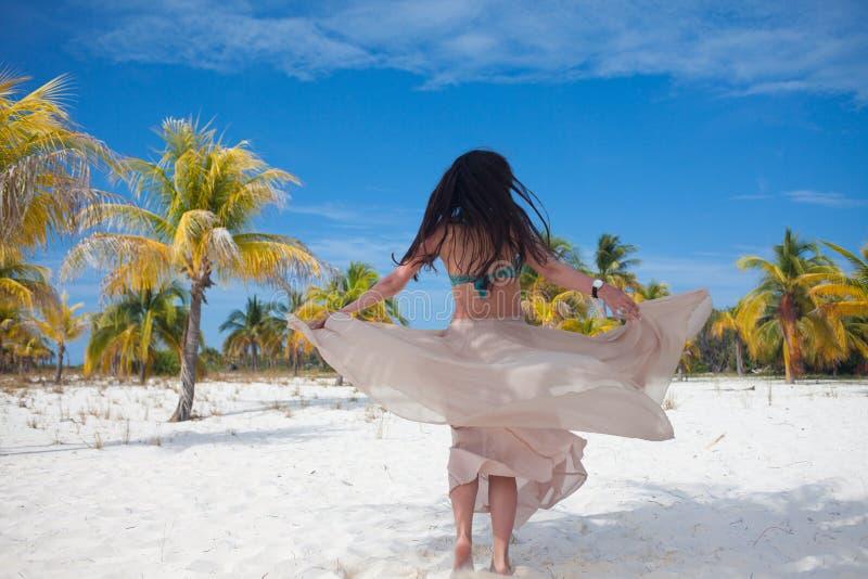 A menina viaja ao mar e está feliz Dança moreno atrativa nova da mulher que acena sua saia contra a paisagem tropical fotos de stock
