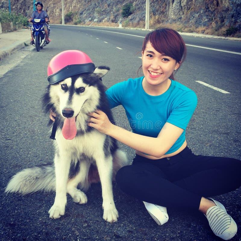 Menina vietnamiana com o cão no chapéu cor-de-rosa imagens de stock royalty free