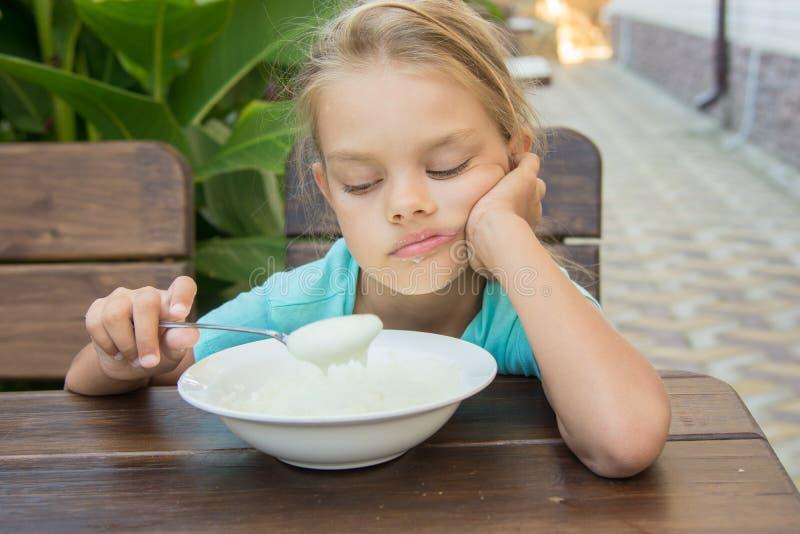 Menina virada da criança de seis anos que olha tristemente na semolina em uma colher no café da manhã fotografia de stock