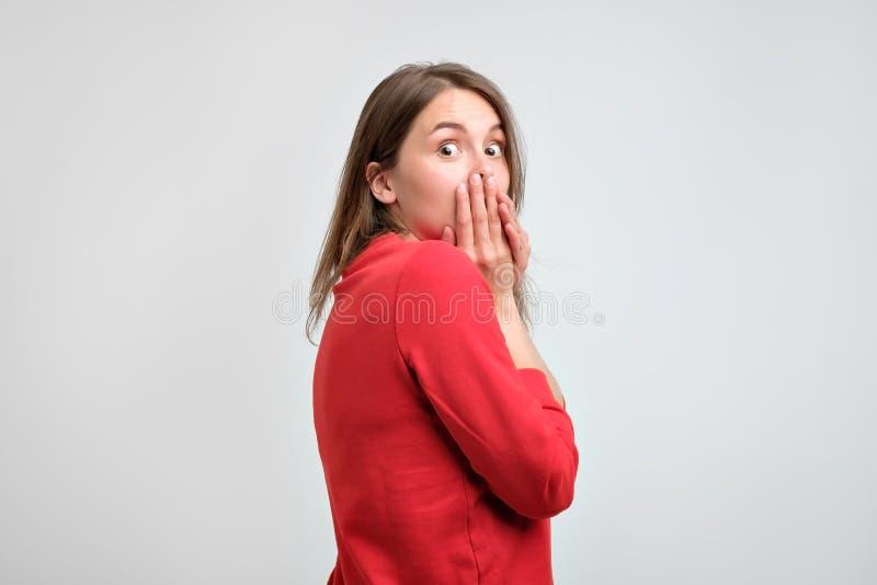 Menina virada na camiseta vermelha que guarda suas mãos em seu queixo que é assustado após o que fez fotos de stock