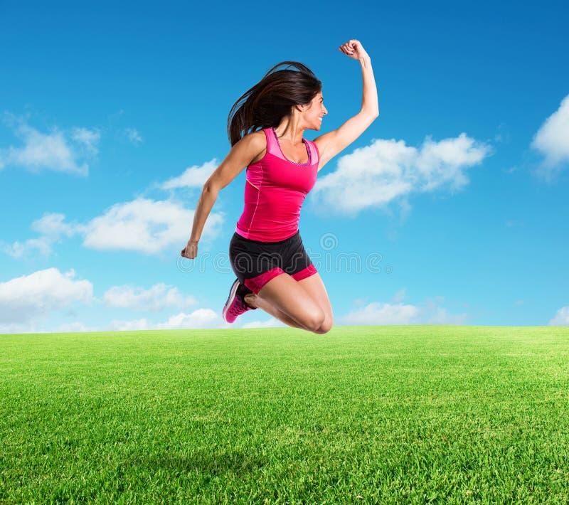 A menina vital e atlética salta imagem de stock