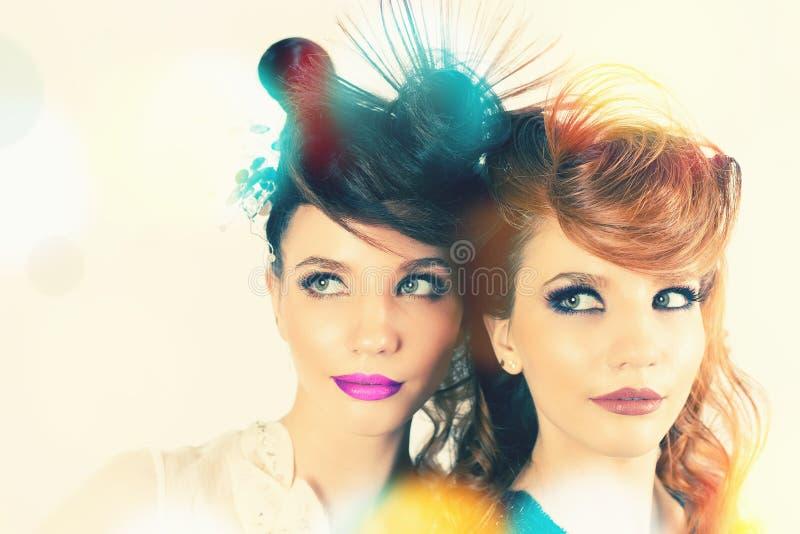 Meninas absolutamente lindos dos gêmeos com composição e penteado da forma foto de stock