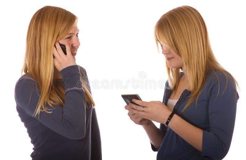 Meninas adolescentes cada um em um telefone de pilha imagens de stock