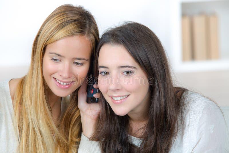 Meninas adolescentes felizes no sorriso do telefone imagens de stock royalty free