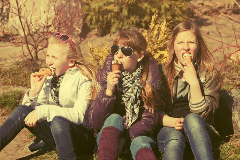 Meninas adolescentes felizes que comem um gelado exterior foto de stock