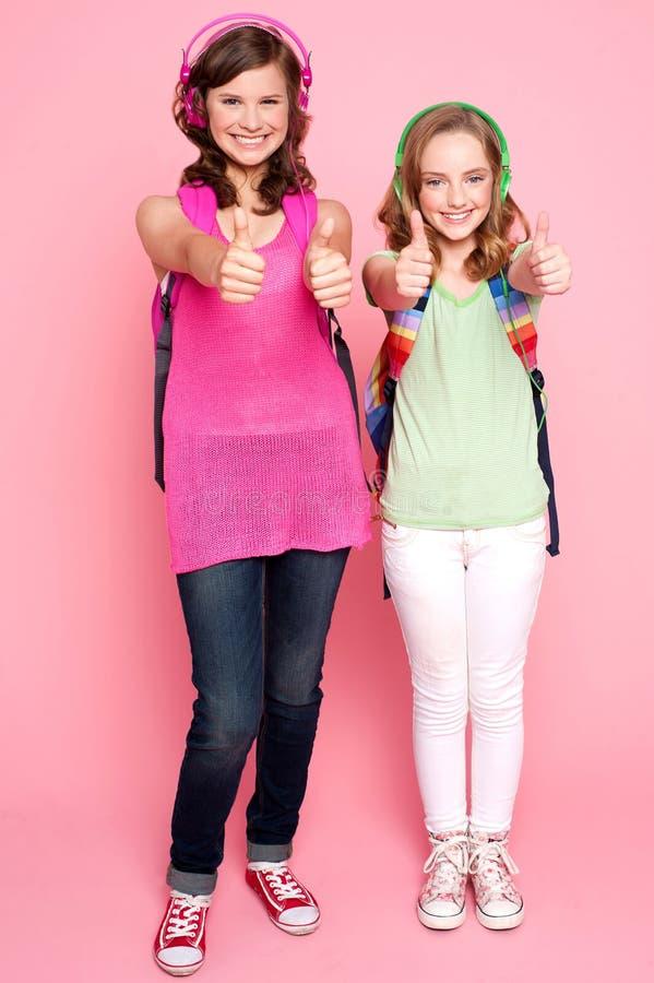 Meninas adolescentes felizes que mostram os polegares acima foto de stock
