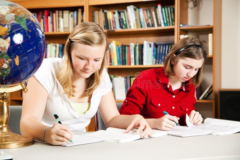 Meninas adolescentes que estudam na escola imagens de stock